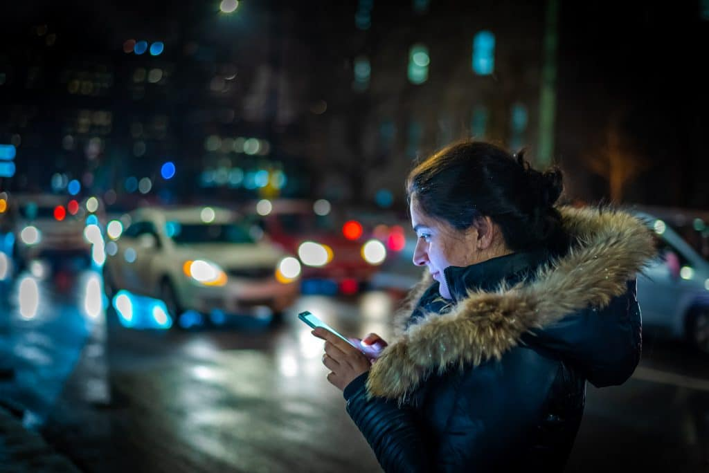 Girl booking online taxi cab uber at night in city street