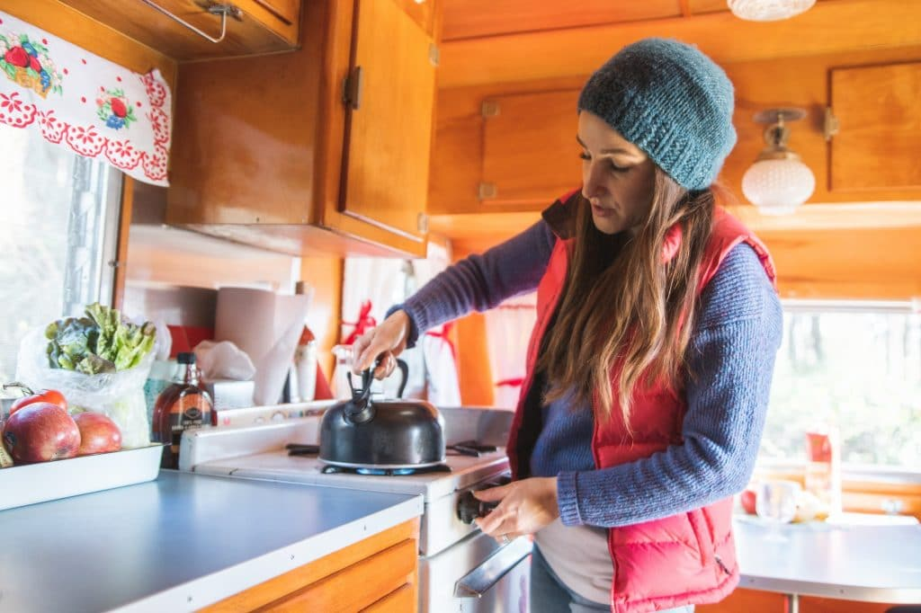 woman in vintage RV camping trailer boiling a kettle on the stove