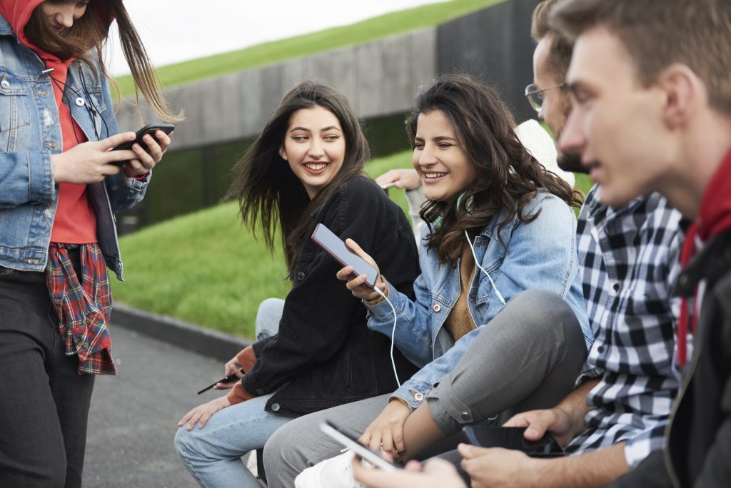 Young people with mobile phone in the city