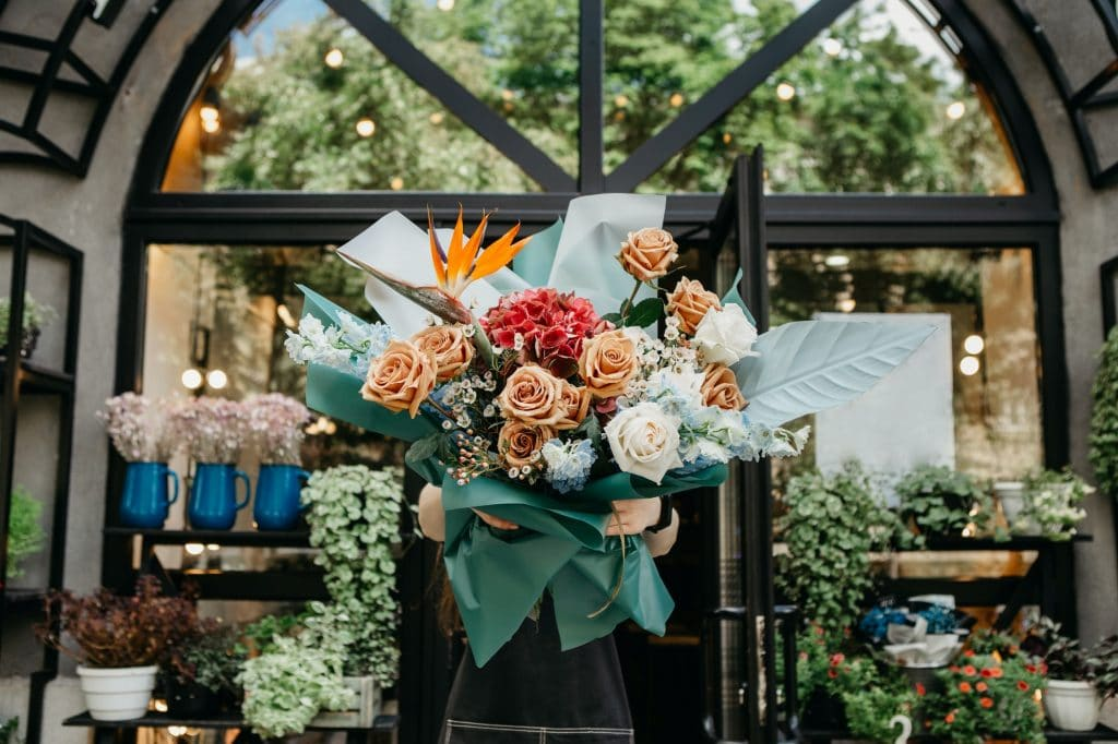 Flowers delivery and florist with her work. Woman holding beautiful multi colored bouquet