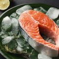 Fresh salmon with ice at dark background