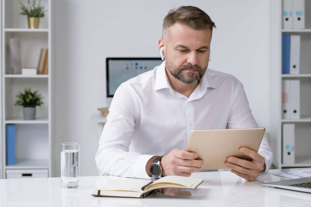 Serious businessman looking at touchpad display while watching online conference