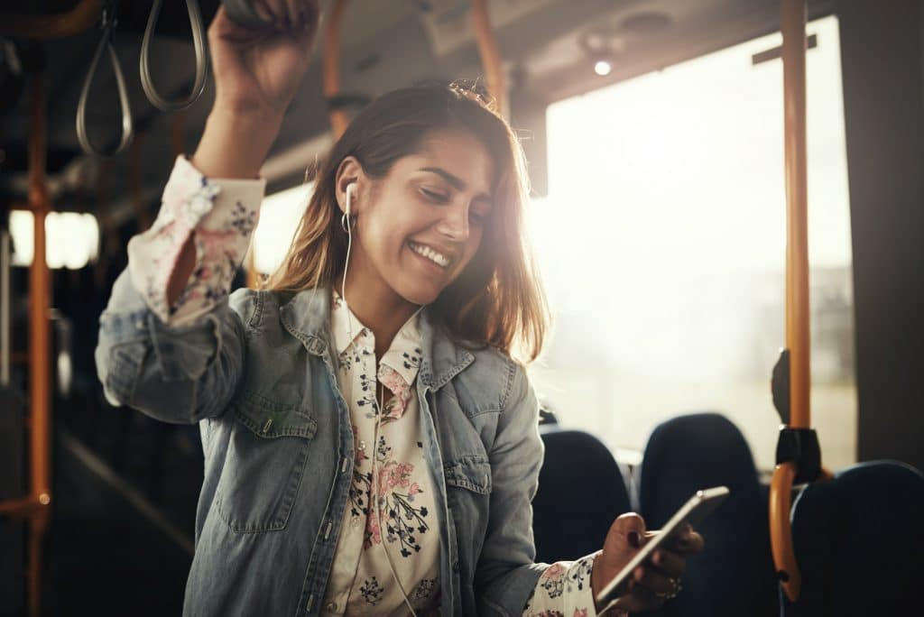 Smiling young woman riding on a bus listening to music
