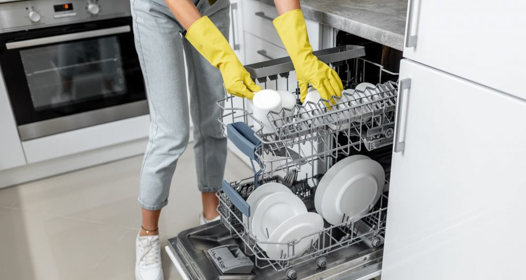 Woman loading dishes into the dishwasher machine