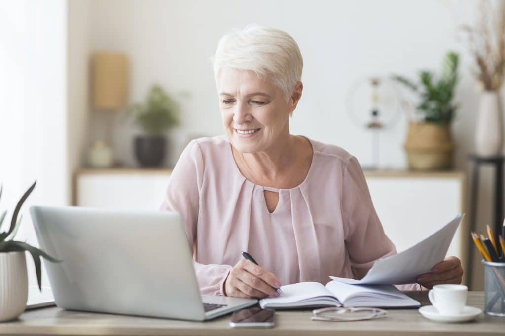 Cheerful senior business woman working with papers at home