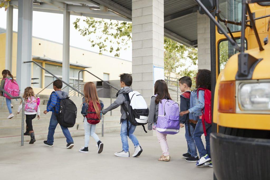 Elementary school kids arrive at school from the school bus