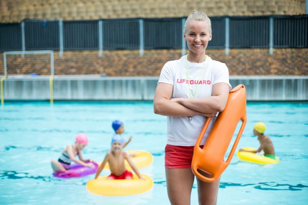 Female lifeguard standing with rescue can at poolside