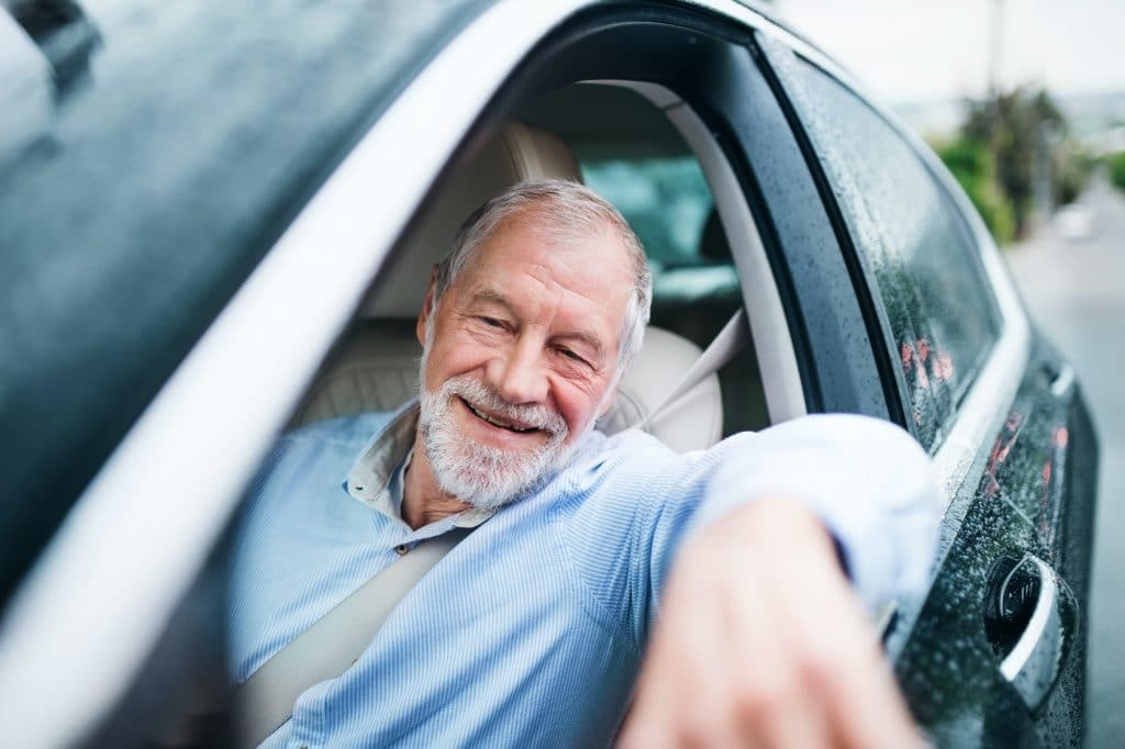 Happy senior man sitting in car in driver seat