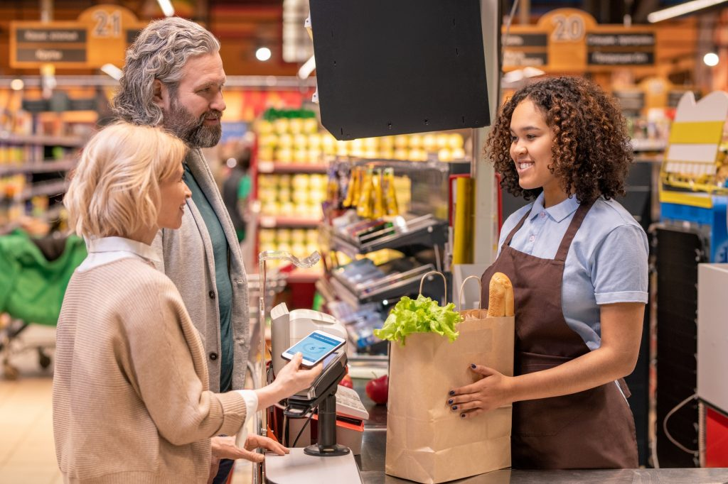 Mature female with smartphone paying for food products in supermarket