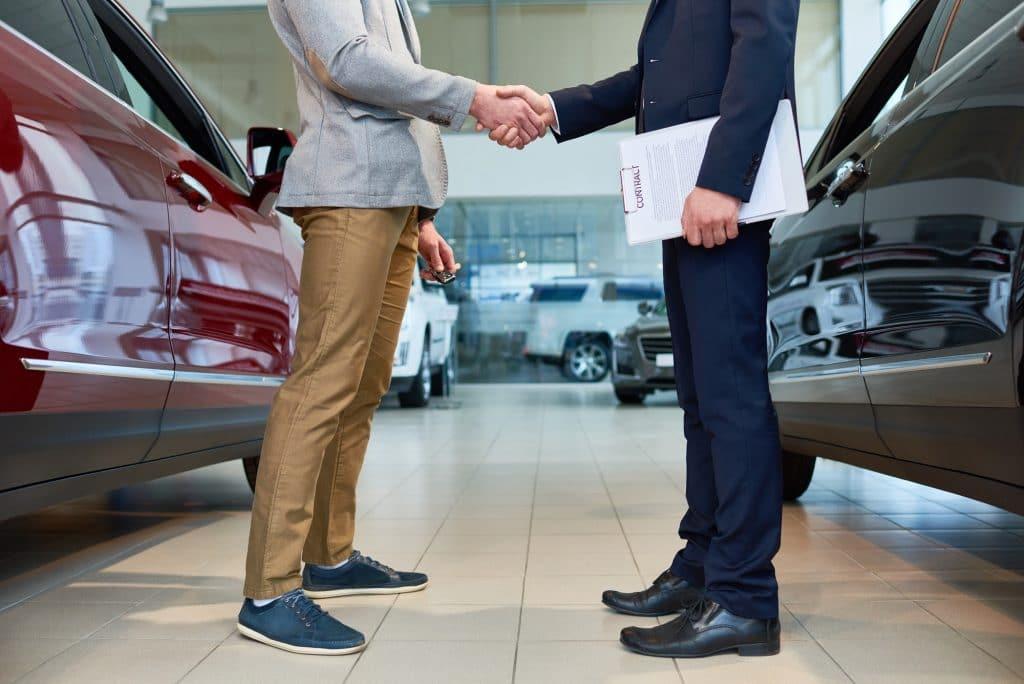 People Shaking Hands in Car Showroom
