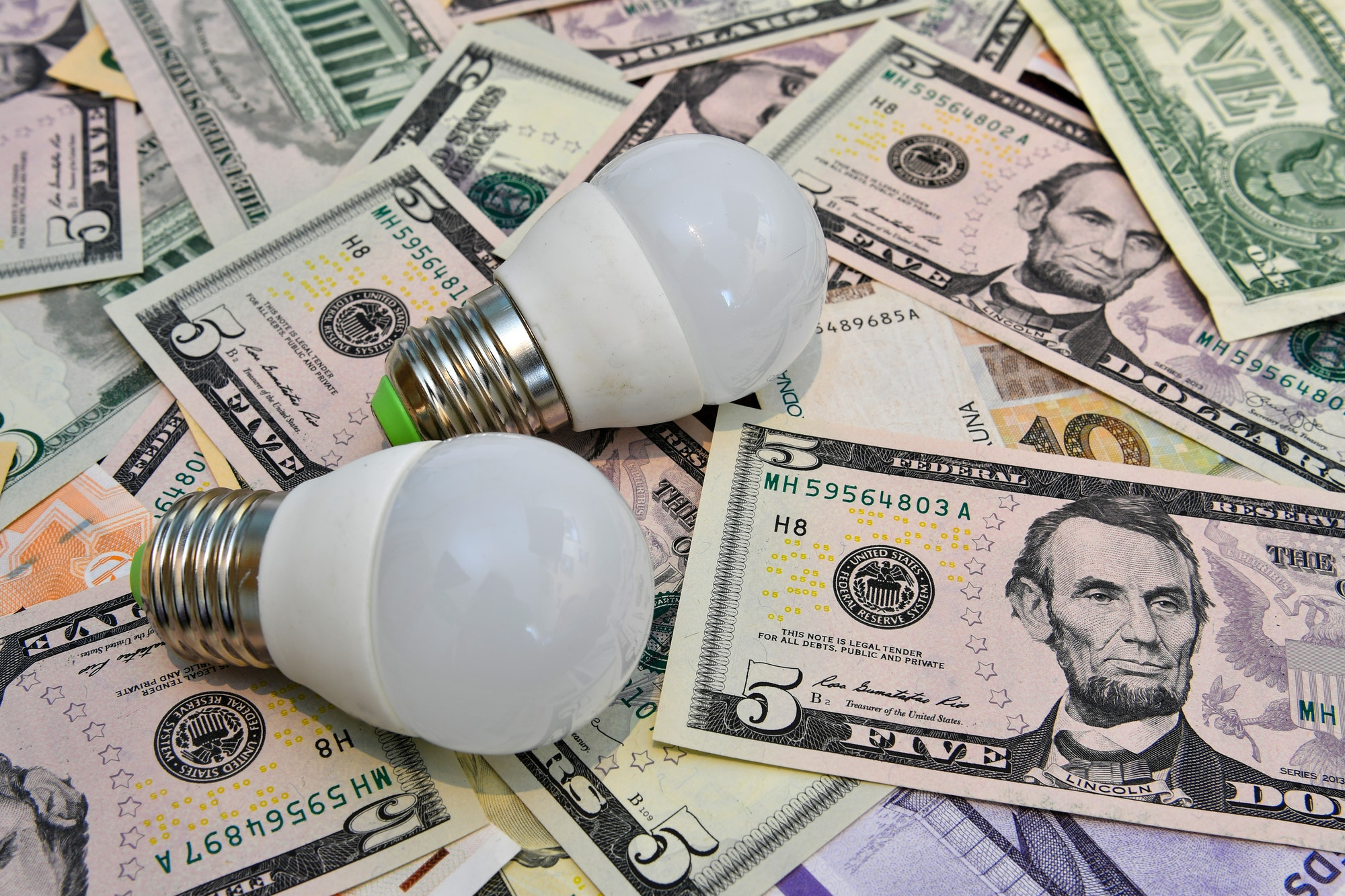 Two LED bulbs in the background of different countries currency notes