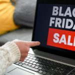Woman pointing her finger toward a laptop screen with a black friday sale sign
