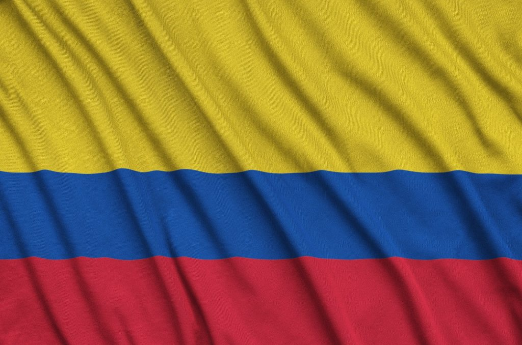 Colombia flag is depicted on a sports cloth fabric with many folds. Sport team waving banner