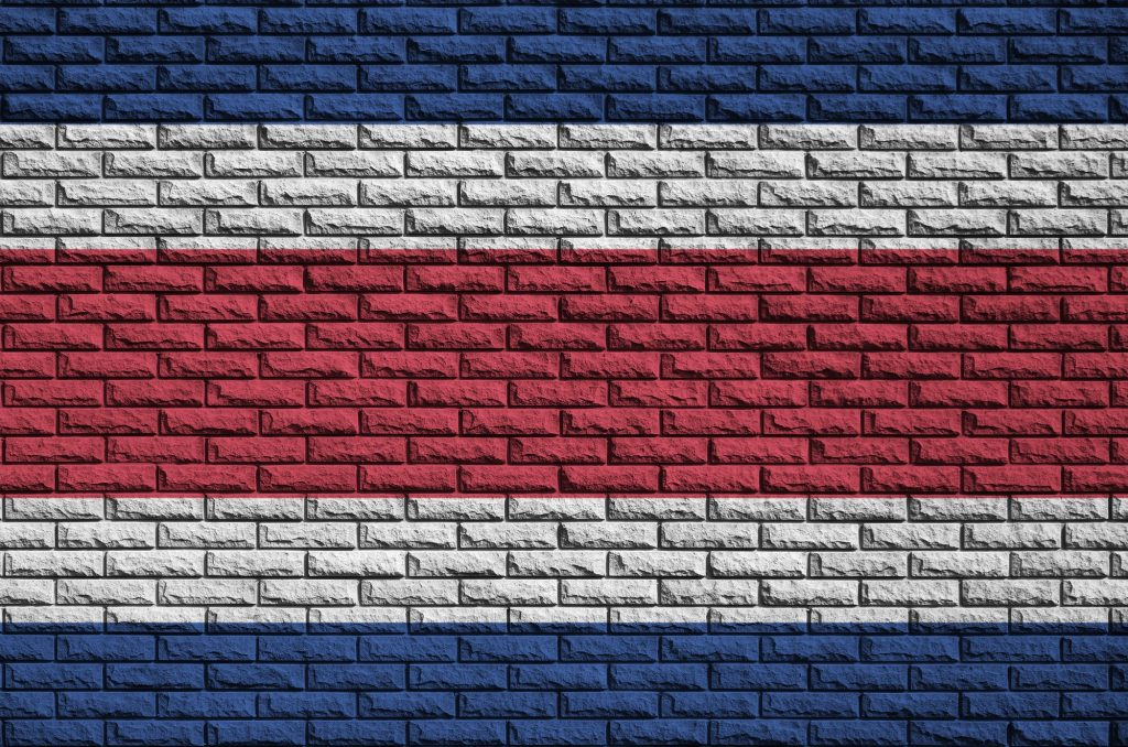 Costa Rica flag is painted onto an old brick wall