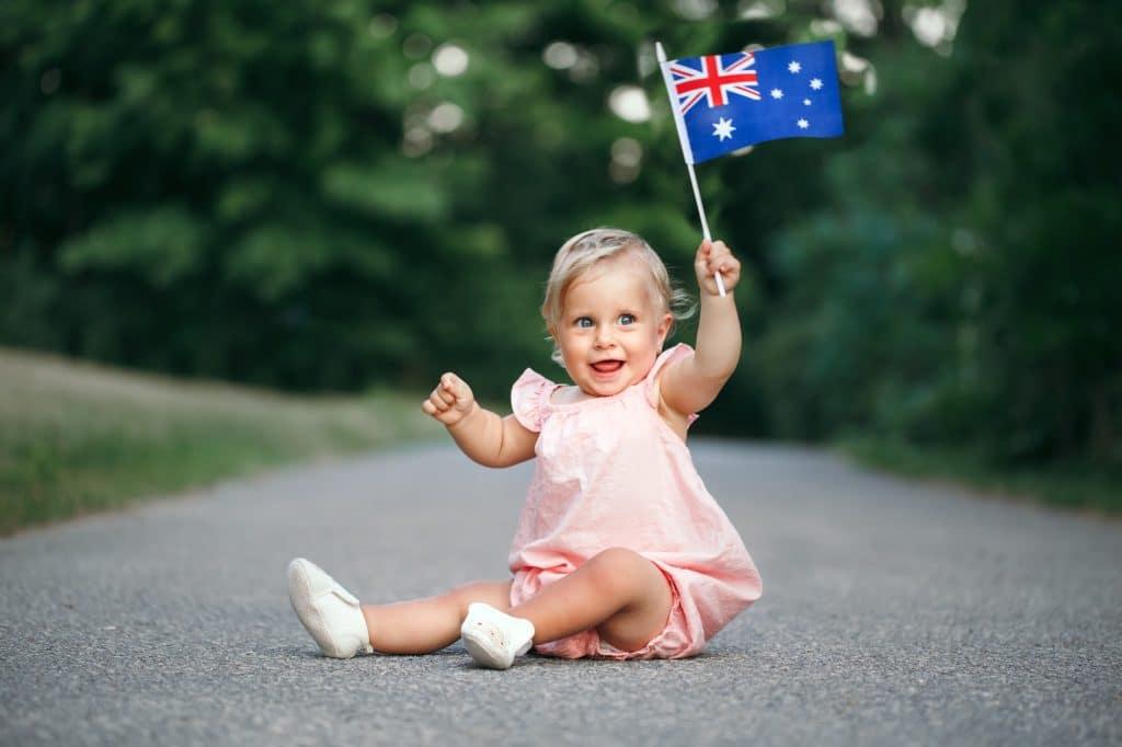 Cute baby girl sitting on ground road street outdoor waving Australian flag. Australia Day holiday.