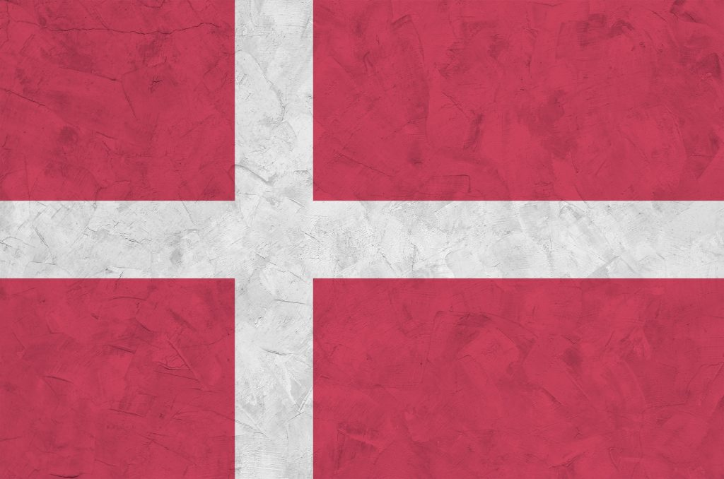 Denmark flag depicted in bright paint colors on old relief plastering wall close up