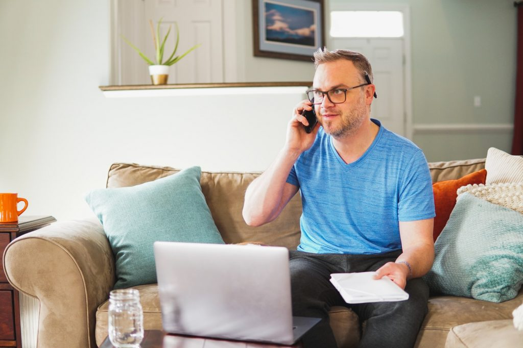 Man working from home on laptop computer talking on phone conference call or paying bills and doing
