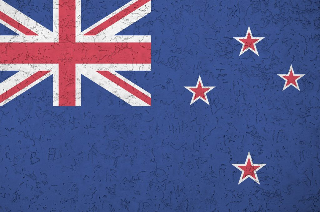 New Zealand flag depicted in bright paint colors on old relief plastering wall close up