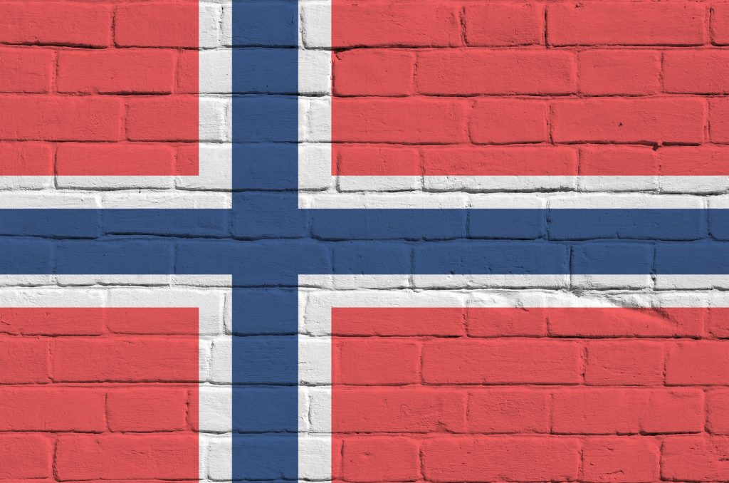 Norway flag depicted in paint colors on old brick wall close up