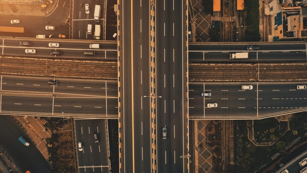 Sun at top down traffic cross road aerial. Urban transportation with cars, trucks, buses at sunlight