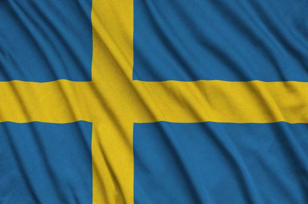 Sweden flag is depicted on a sports cloth fabric with many folds. Sport team waving banner