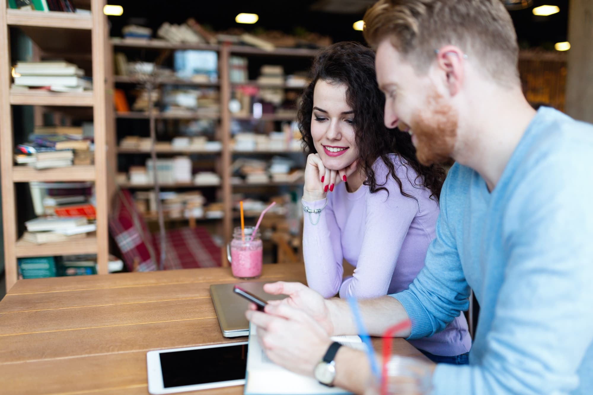 Attractive students learning together in coffee shop