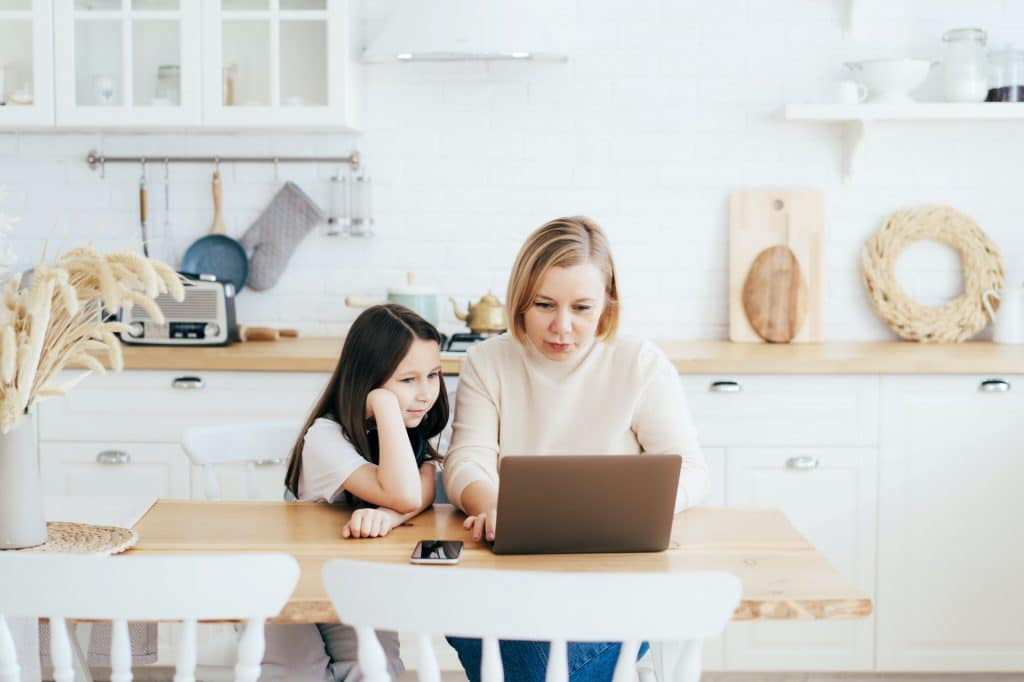 Mom and daughter at the table in the kitchen with a laptop work, study and communicate online.