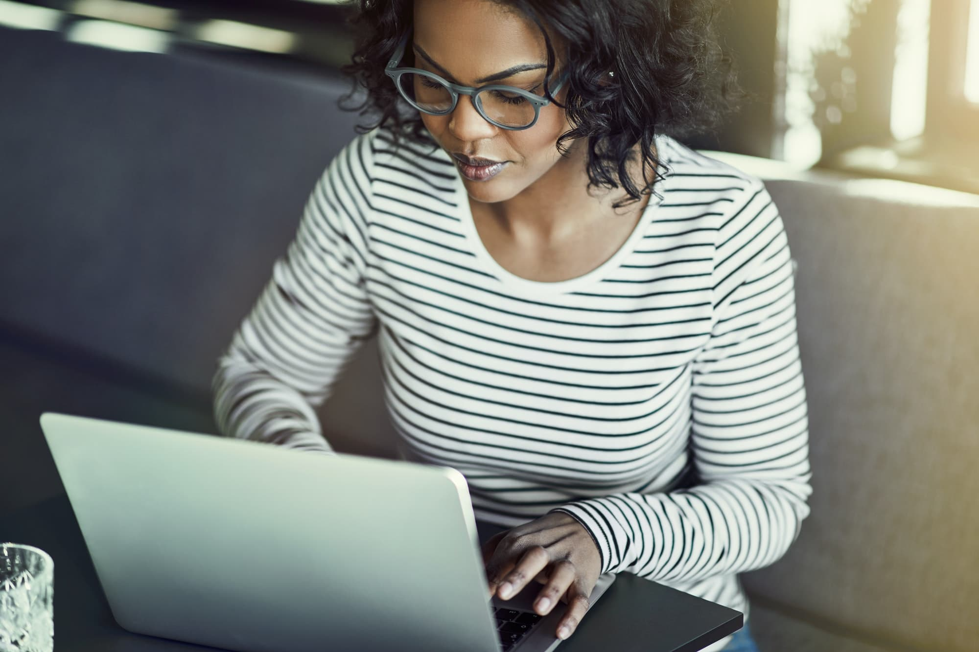 Young African woman browsing online with a laptop