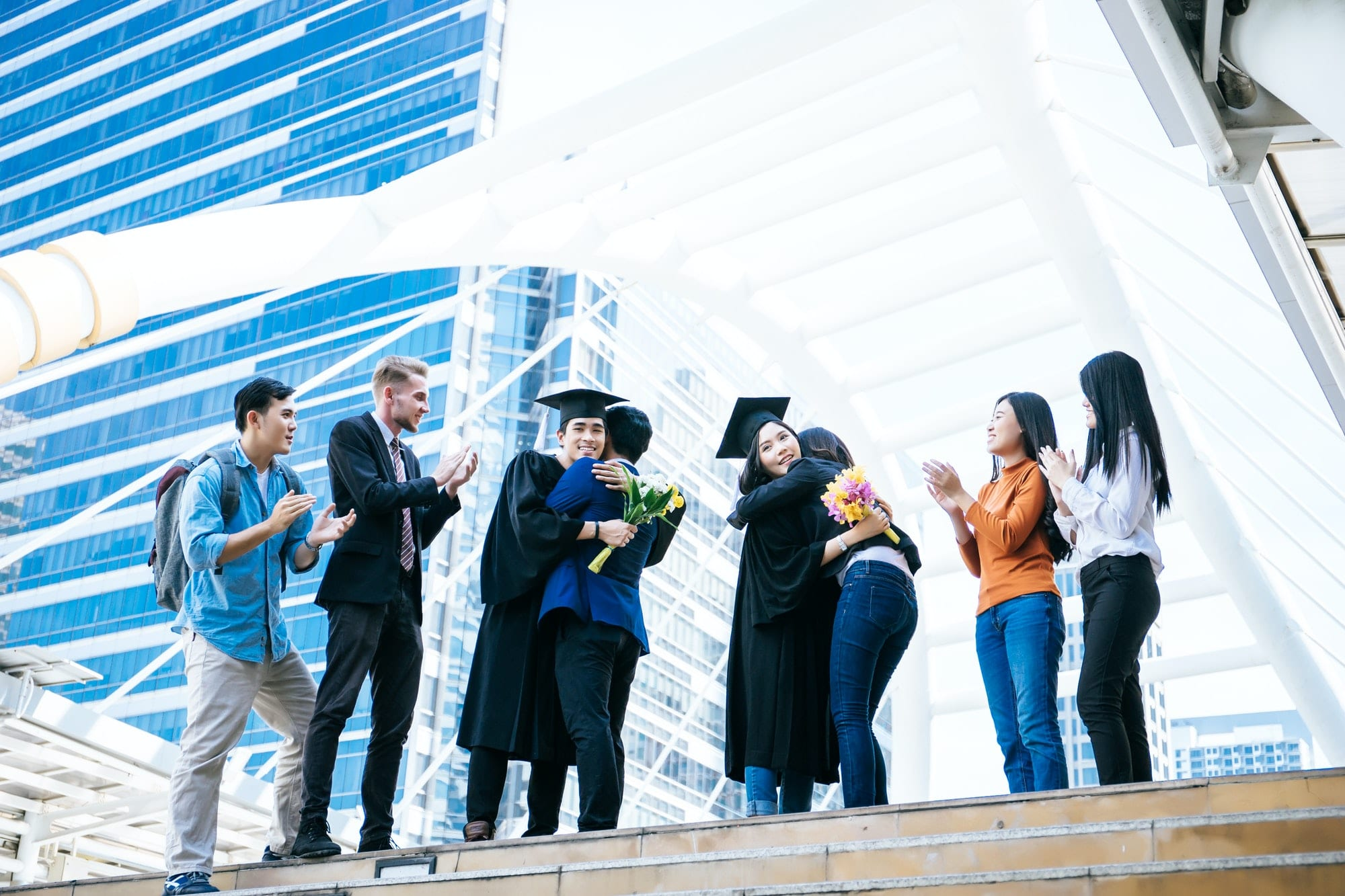 Asian students graduate being congratulated by their parent at graduation ceremony