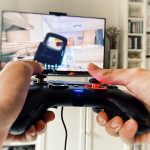 Playing videogame PlayStation holding teen hands on controller