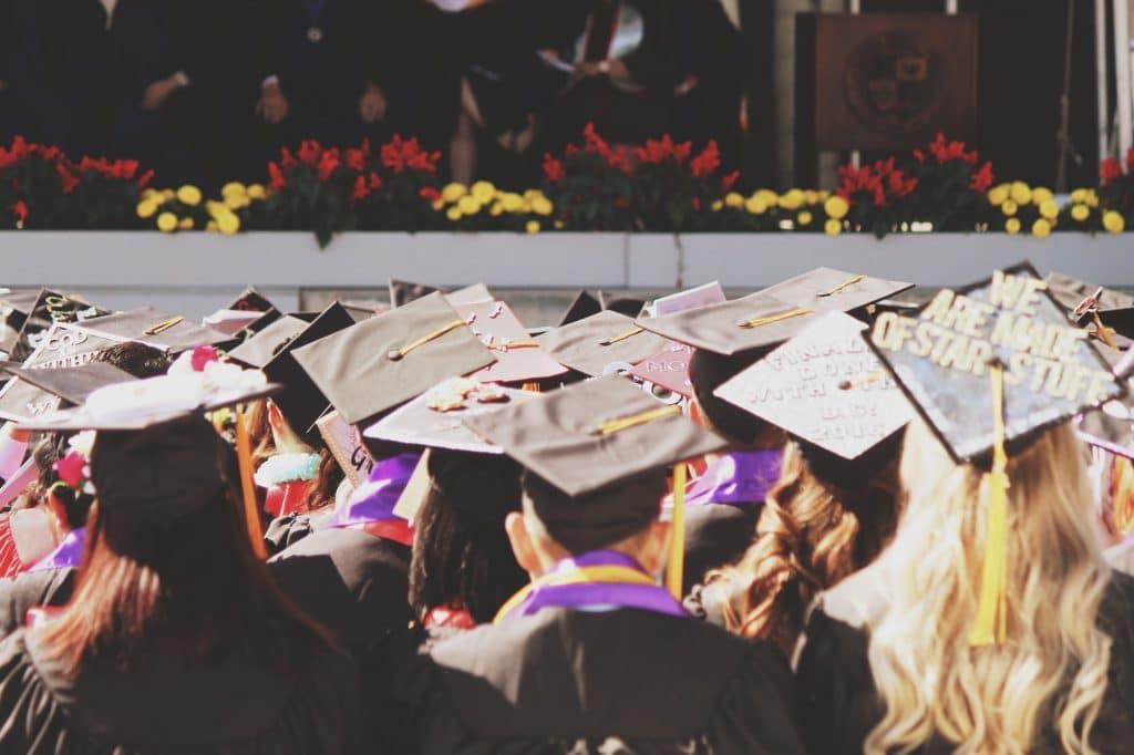Young college high school graduates at graduation ceremony