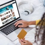 cropped image of woman holding credit card and using laptop with amazon on screen