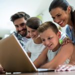 Happy family using laptop in the living room