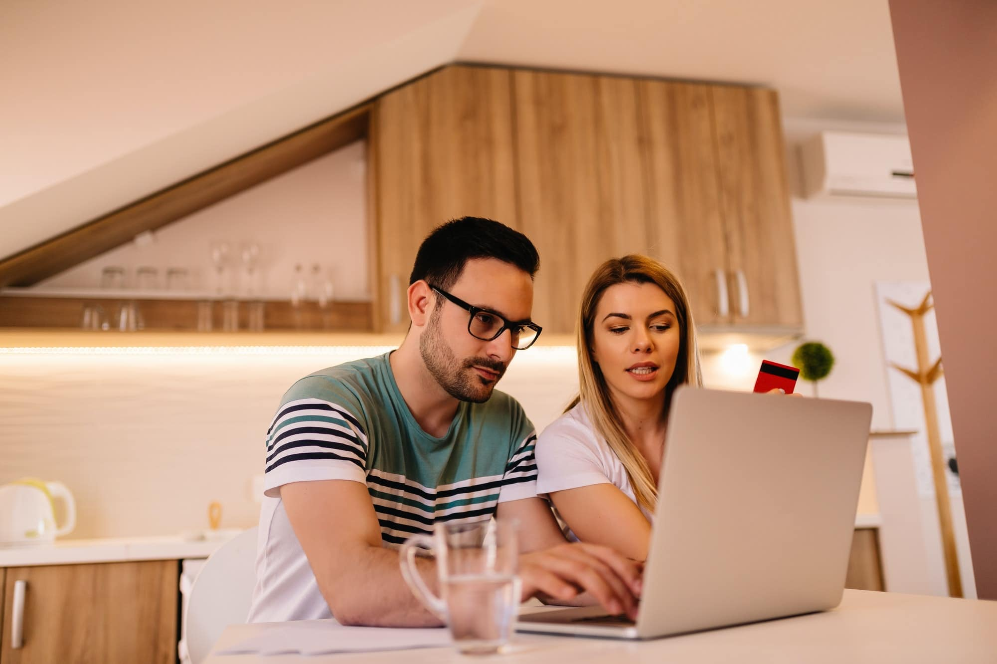 Serious young couple paying their bills online from home