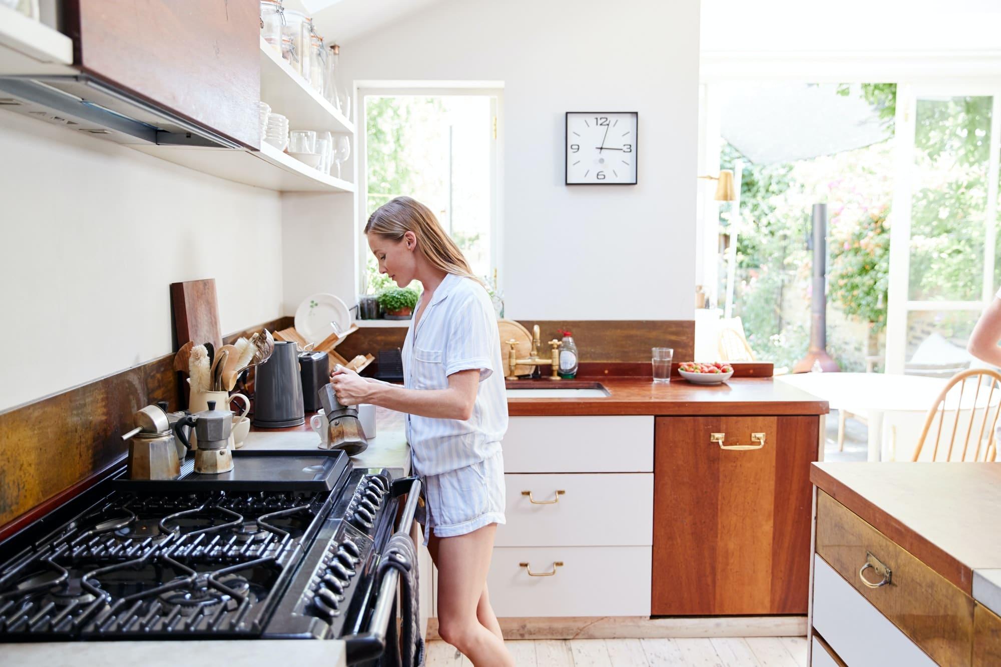 Woman Wearing Pajamas At Home In Kitchen Making Fresh Coffee
