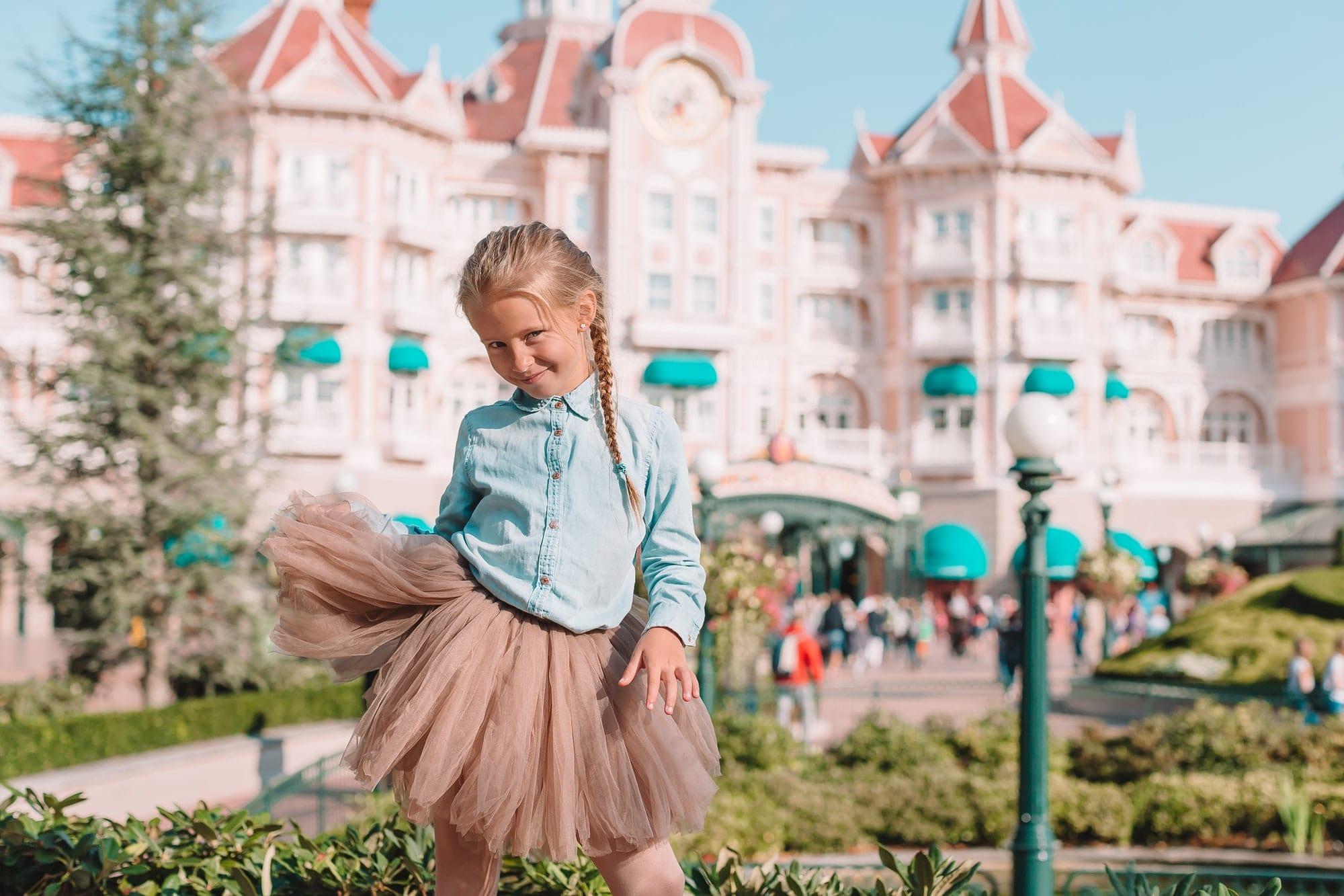 Little adorable girl in Cinderella dress at fairy-tale Disneyland park