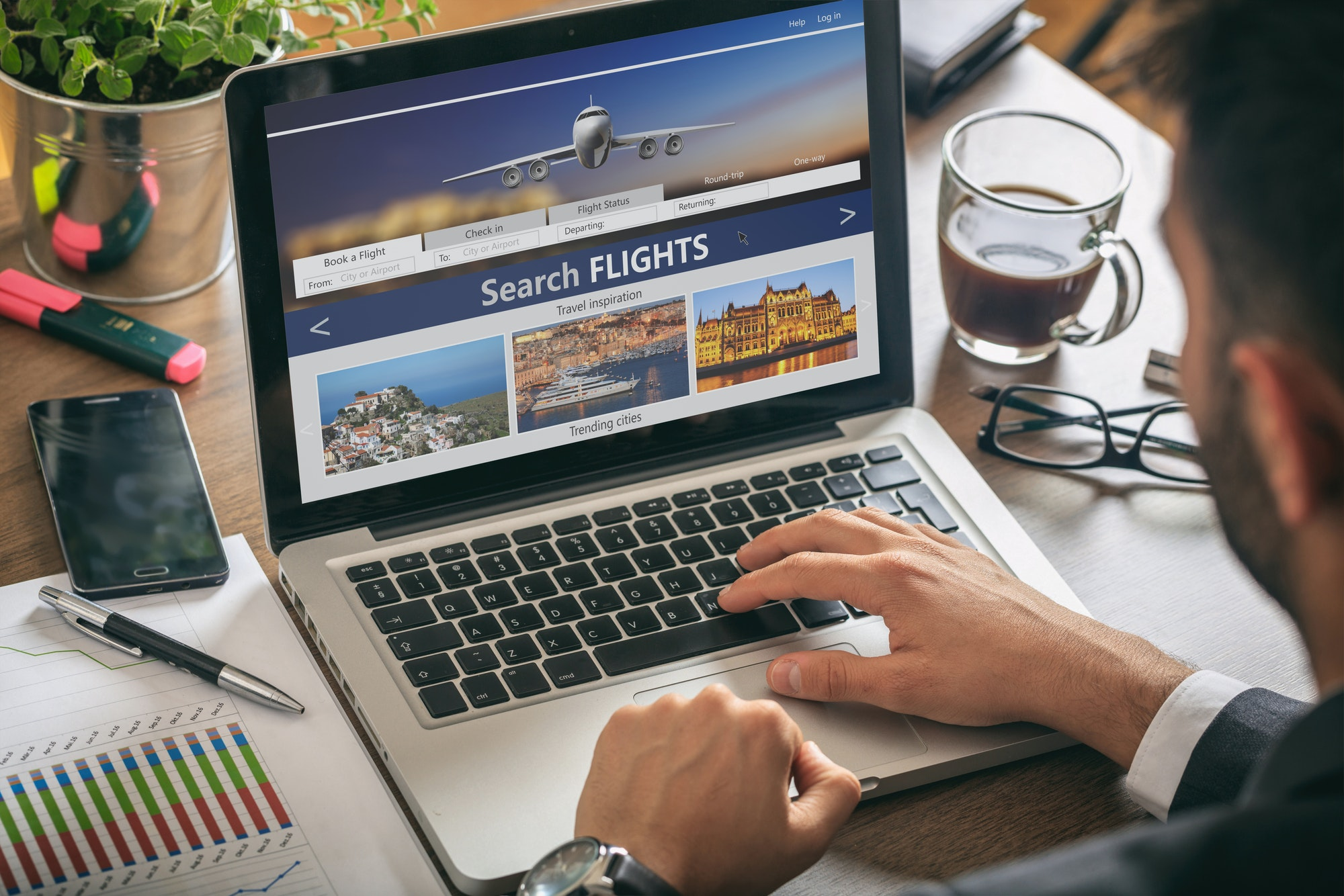 Man working with a computer, search flights on the screen, office business background.