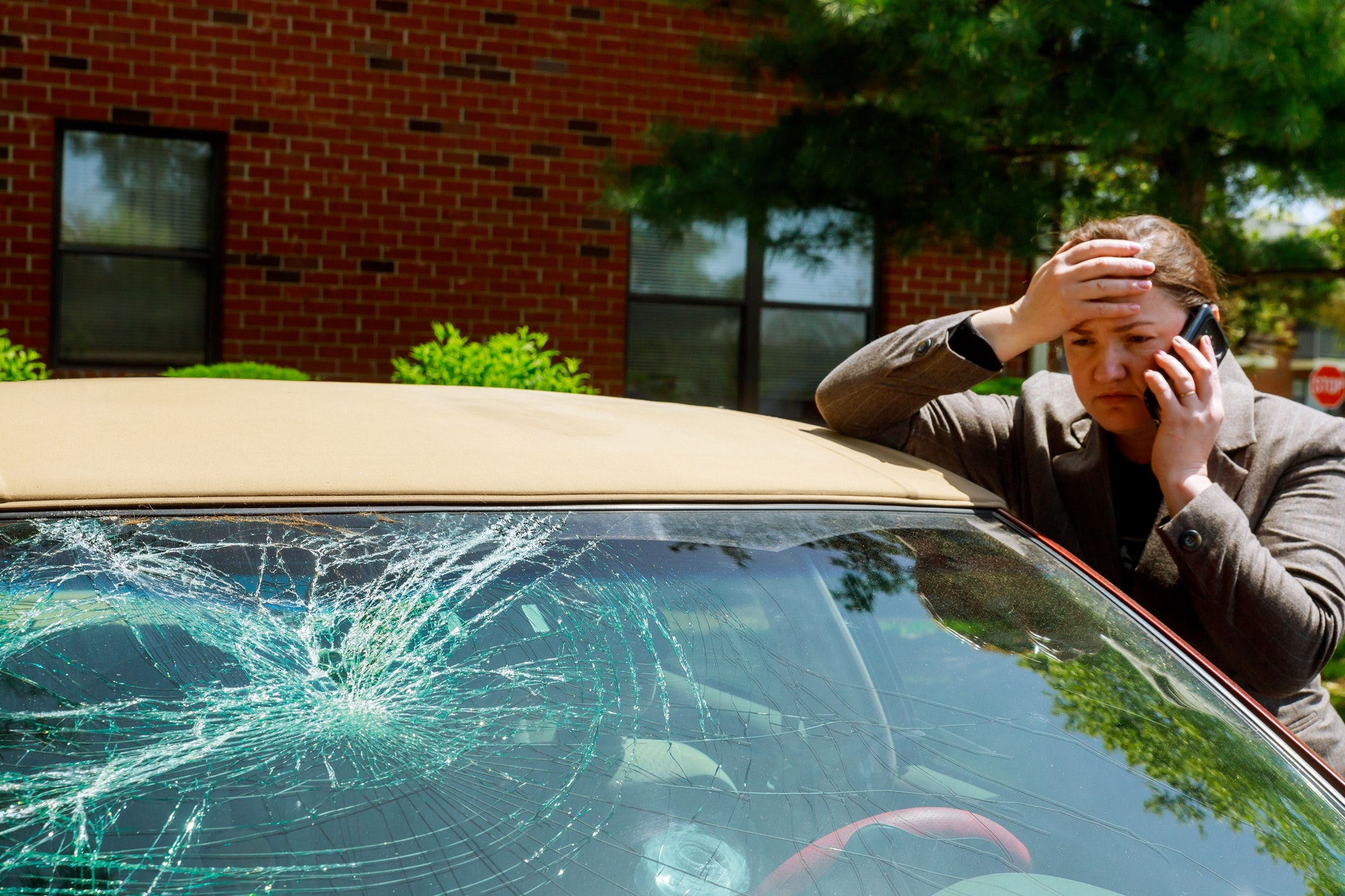 Woman making a phone call next to broken windshield after a car accident