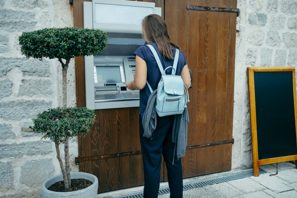Back view of a Woman traveler with blue backpack takes out money at an ATM in Europe
