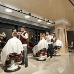 Male hairdressers servicing clients in barber shop