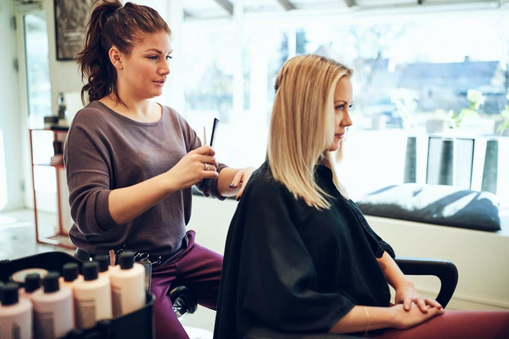 Young blonde woman getting her hair cut in a salon