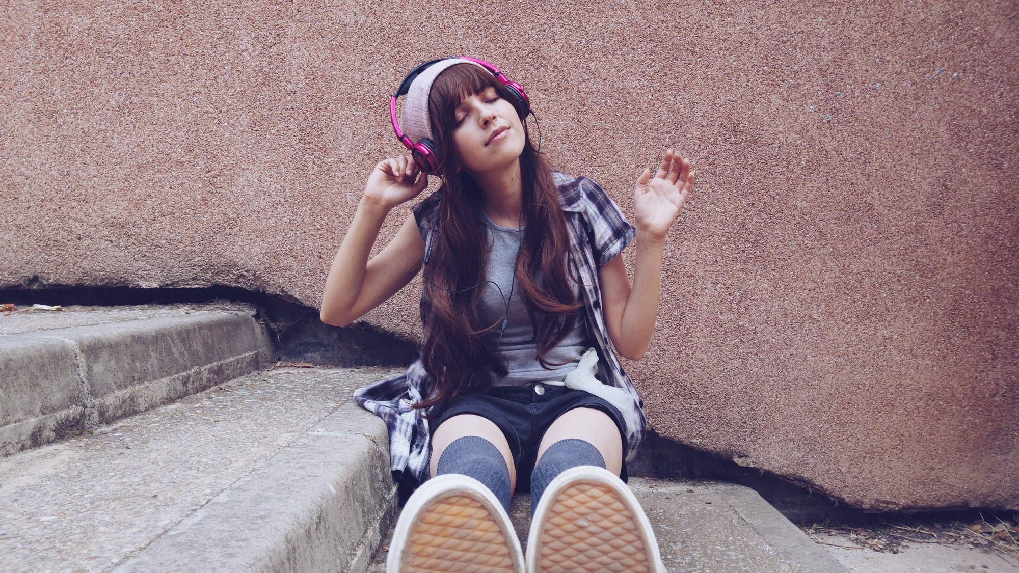 Young student woman listening to music in a park