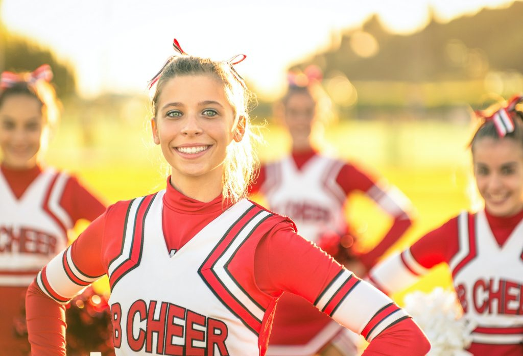 Portrait of an happy young cheerleader in action outdoors