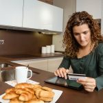 Woman with electronic tablet and credit card buying online