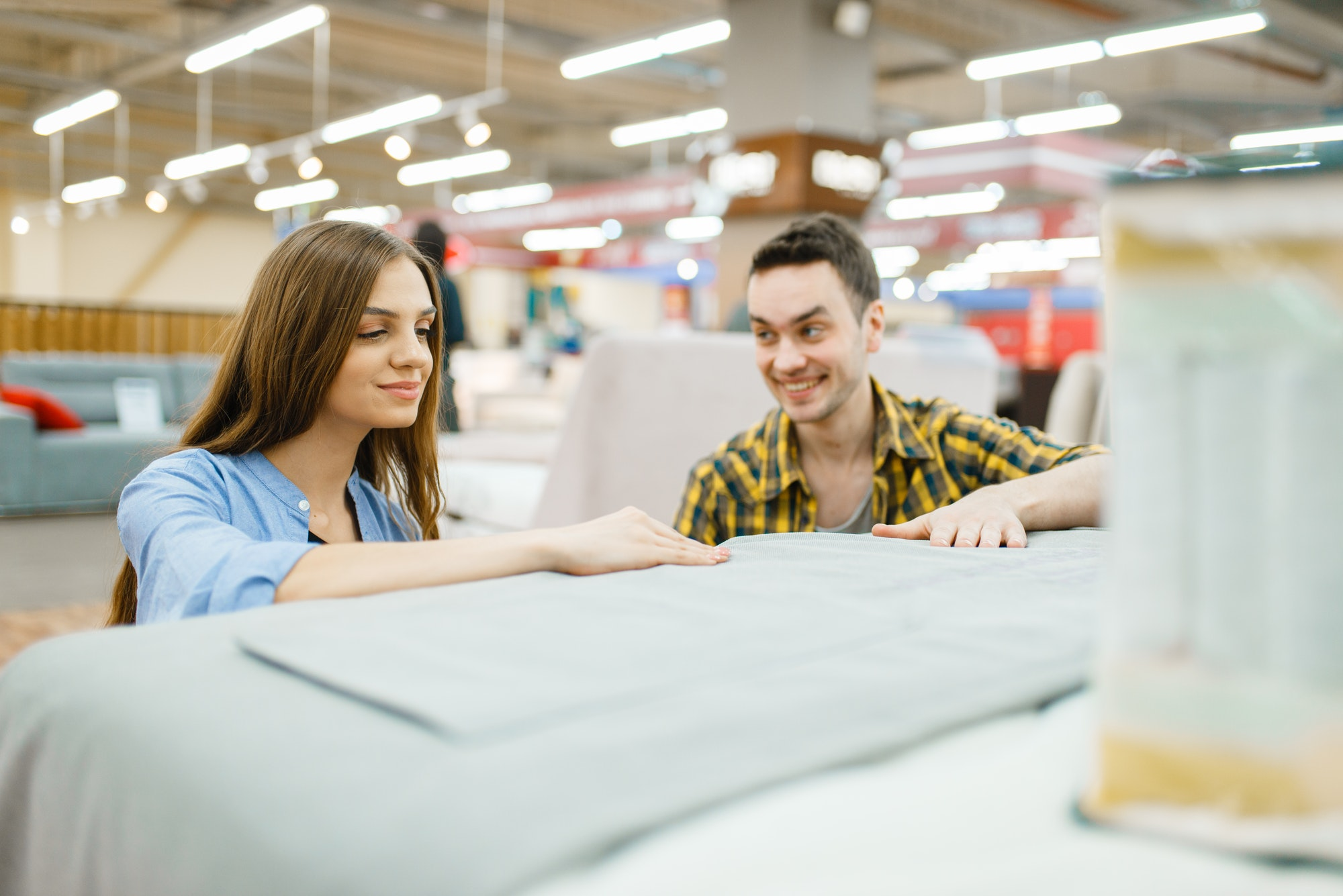 Couple buying blanket for bed in furniture store