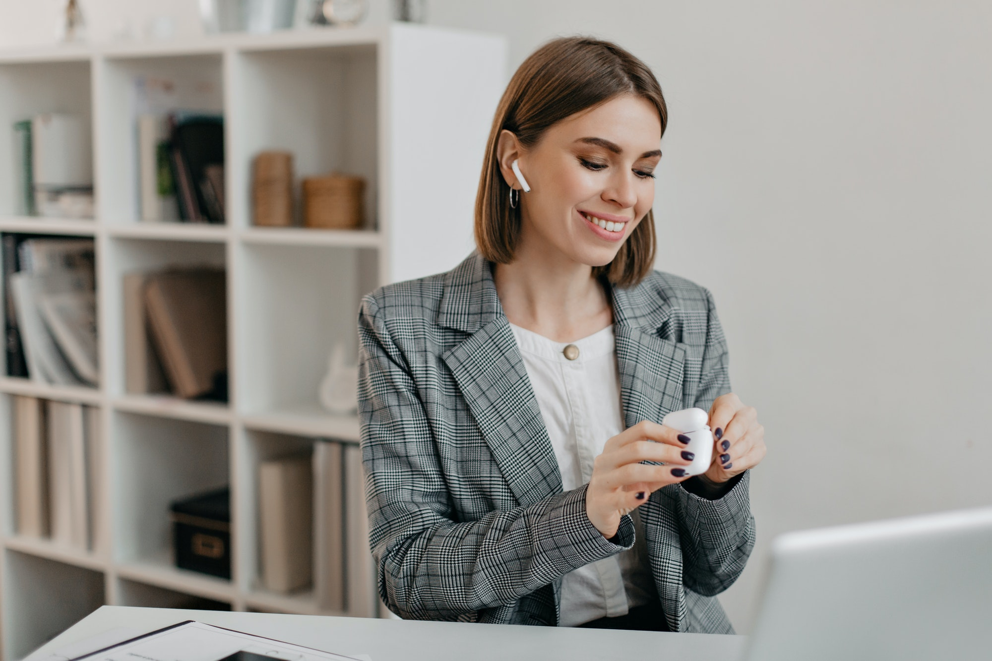 Portrait of smiling woman in office outfit putting on airpods to communicate with customers