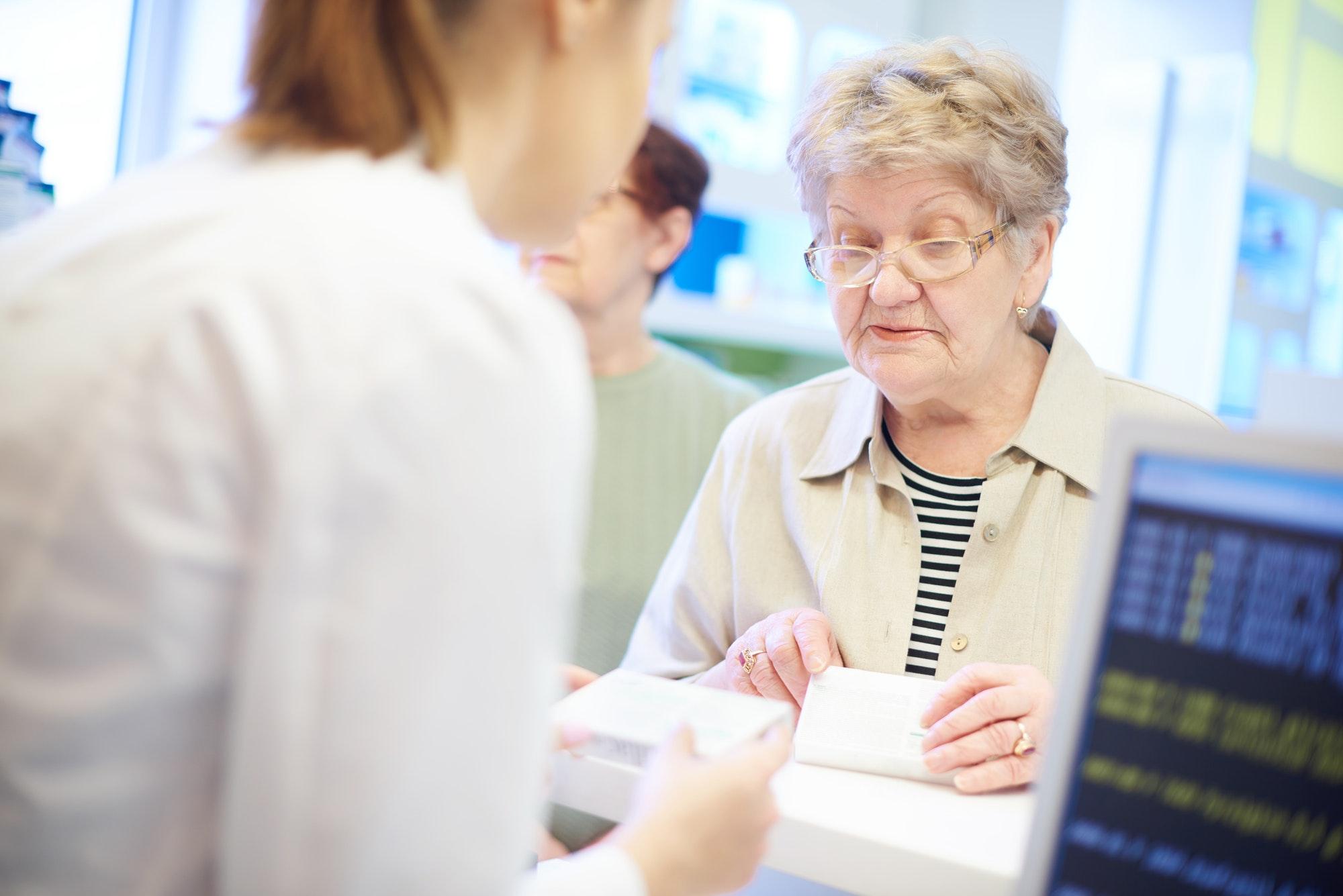 Senior customer at cash register with pharmacist
