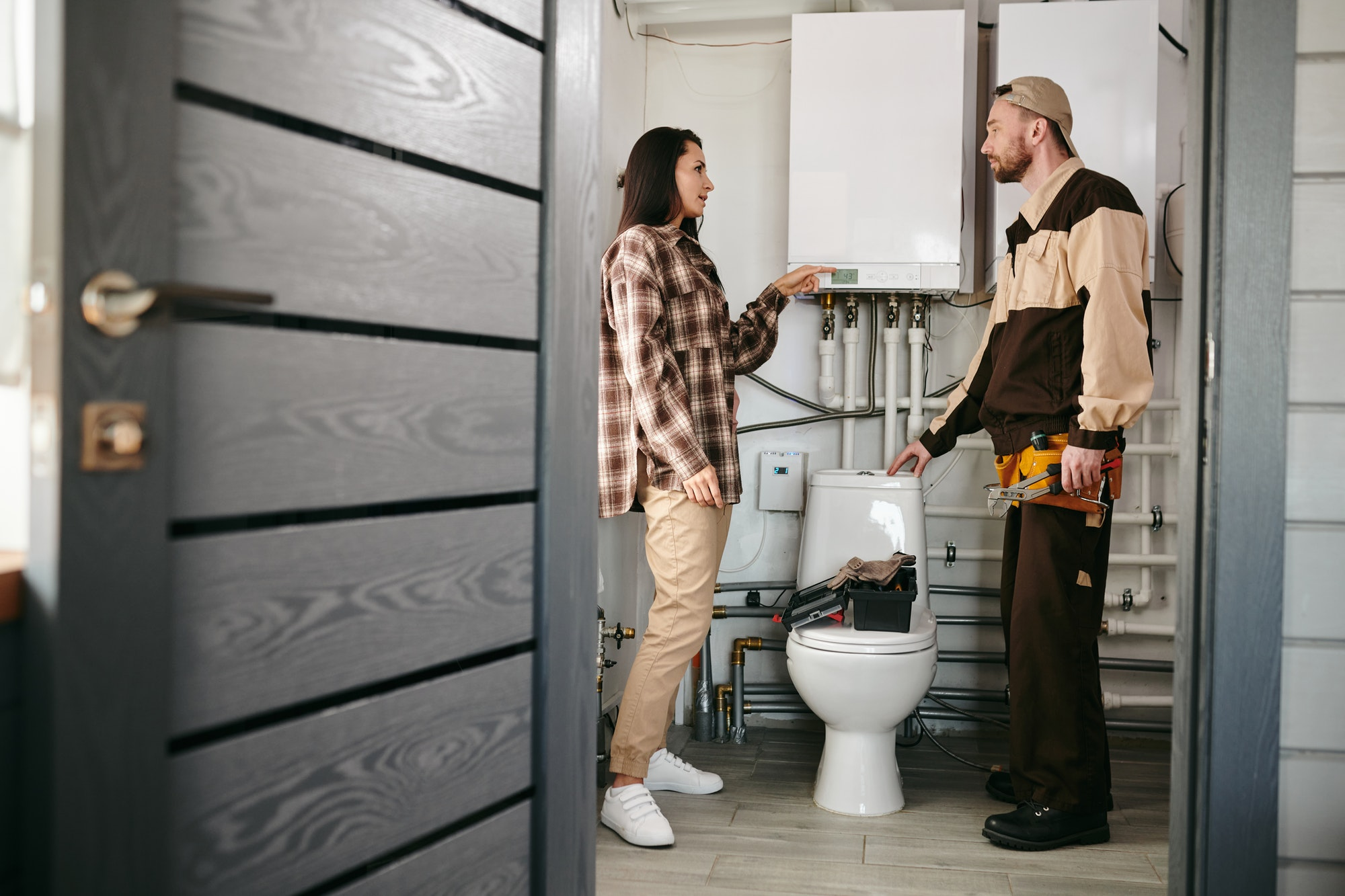 A man and woman standing in a bathroom and discussing problem with plumbing equipment
