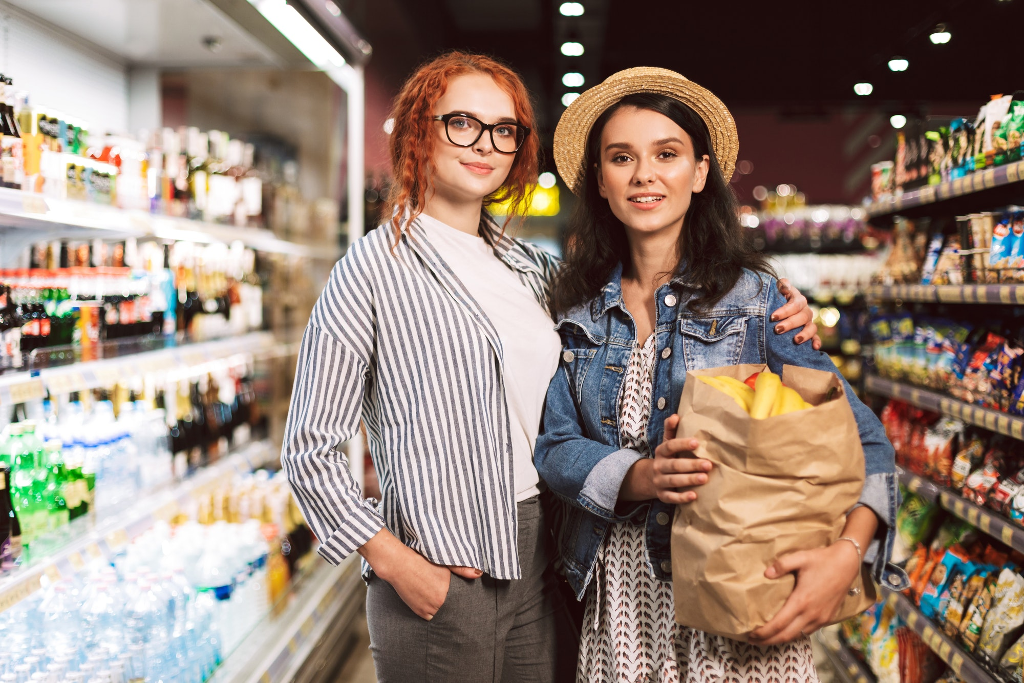 Beautiful girls with paper grocery bag full of products happily