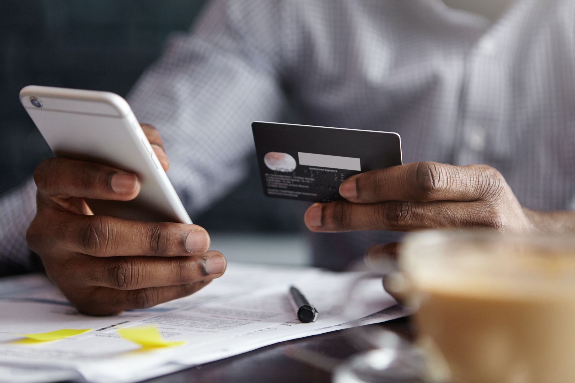 Cropped shot of African-American businessman paying with credit card online making orders via Intern